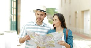 Couple of tourists walking checking map in a town street stock footage
