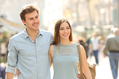 Couple of tourists walking in a city street. Couple of tourists taking a walk in a city street sidewalk in a sunny day Royalty Free Stock Image