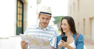Couple of tourists walking comparing phone and map stock video