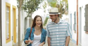 Couple of tourists walking and talking in a town. Street on vacation stock video footage
