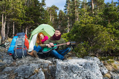 Couple tourists woman and man sitting at the camp in forest and Stock Photography
