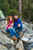 Couple tourists woman and man sitting at the camp in forest and Royalty Free Stock Photography