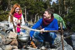 Couple tourists woman and man sitting at the camp in forest and Stock Photo