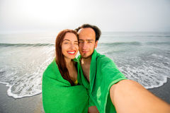 Couple in towels on the beach Stock Images