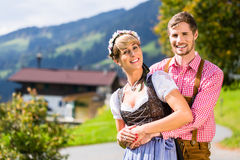 Couple in Tracht standing on meadow in alp mountains Royalty Free Stock Photography