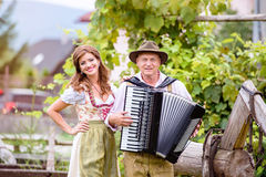 Couple in traditional bavarian clothes with accordion, green gar Royalty Free Stock Photos