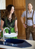 Couple in traditional bavarian clothes standing in kitchen Stock Image