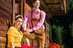Couple in traditional clothing front of mountain hut Royalty Free Stock Image