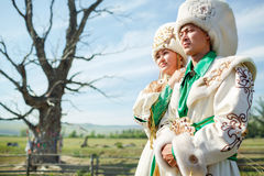 Couple in traditional dress, on background epic ancient tree at the middle of rural landscape. Royalty Free Stock Image
