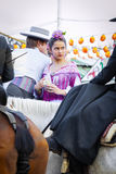 Couple in traditional dress riding at the April Fair Seville Stock Photos