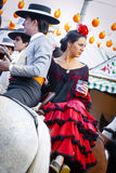 Couple in traditional dress riding at the April Fair Seville Stock Photography