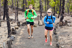 Couple trail running in forest Stock Image