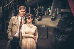 Couple on train station platform. Vintage style couple near steam locomotive Stock Photos