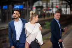 Couple at train station and woman flirting with another man Stock Images