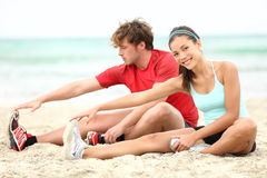 Couple training on beach. Stretching legs after running. Young men and women during summer workout. Asian female fitness model, Caucasian male fitness model Stock Photo