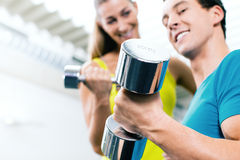 Couple training for fitness in gym with weights Stock Photo