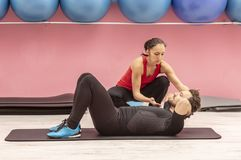 Couple Training in a Gym. Young men helped by his coach doing sit-ups in a gym Royalty Free Stock Photography