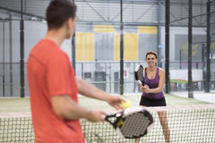 Couple training paddle tennis in court with racket and balls Stock Image