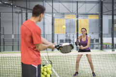Couple training paddle tennis in court with racket and balls Royalty Free Stock Images