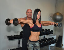 Couple Training. Trainer helps client train with weights. Couple training together Stock Photography