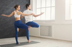 Couple training yoga in tree pose. Fitness, men and women training yoga in tree pose. Young couple makes relaxing exercise at window, back view, copy space royalty free stock image