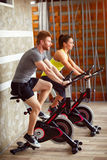 Couple trains on bike in gym Stock Photos