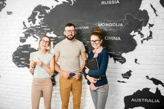 Couple with travel agent at the office. Portrait of a young couple of travelers choosing a summer strip standing with travel agent on the world map background Royalty Free Stock Photo