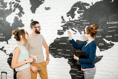 Couple with travel agent at the office. Young couple of travelers choosing a summer trip with travel agent pointing on the world map Stock Photos
