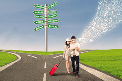 Couple travel at cross road using e-tablet Royalty Free Stock Images