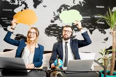 Couple of travel managers dreaming at the office. Couple of travel managers dreaming with colorful bubbles above the head sitting at the agency office with world Royalty Free Stock Photo