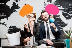 Couple of travel managers dreaming at the office. Couple of travel managers dreaming with colorful bubbles above the head sitting at the agency office with world Royalty Free Stock Image