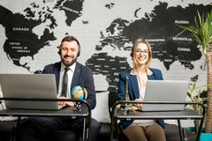 Couple of travel managers working at the office. Couple of travel managers working online with laptops and headsets at the agency office with world map on the Stock Photography