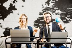 Couple of travel managers working at the office. Couple of travel managers working online with laptops and headsets at the agency office with world map on the Stock Photos
