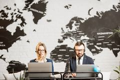 Couple of travel managers working at the office. Couple of travel managers working online with laptops and headsets at the agency office with world map on the Royalty Free Stock Image