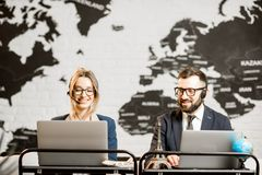 Couple of travel managers working at the office. Couple of travel managers working online with laptops and headsets at the agency office with world map on the Stock Images