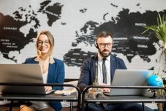 Couple of travel managers working at the office. Couple of travel managers working online with laptops and headsets at the agency office with world map on the Royalty Free Stock Photo