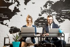 Couple of travel managers working at the office. Couple of travel managers working online with laptops and headsets at the agency office with world map on the Royalty Free Stock Photos