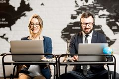 Couple of travel managers working at the office. Couple of travel managers working online with laptops and headsets at the agency office with world map on the Stock Image