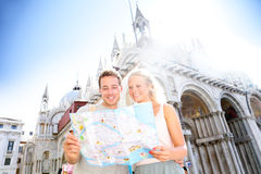 Couple on travel reading map on in Venice, Italy. On Piazza San Marco in front of Saint Mark's Basilica. Happy young couple on travel vacation in Europe. Happy stock photos
