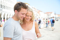 Couple on travel using tablet computer in Venice. Happy young couple traveling using travel app looking at map or similar smiling joyful. Young women and men Stock Photo