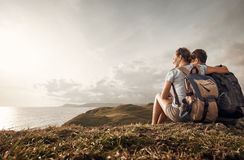 Couple travelers with backpacks look sunset on top of a mountain. Hikers with backpacks enjoying view of sunset in ocean. Traveling along mountains and coast Royalty Free Stock Image