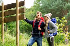 Couple of travelers with backpacks at signpost. Travel, tourism, hiking and people concept - couple of travelers with backpacks looking at signpost royalty free stock image