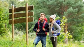 Couple of travelers with backpacks at signpost. Travel, tourism, hiking and people concept - couple of travelers with backpacks looking at signpost royalty free stock images