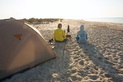 Couple of travelers drinking coffee next to tent. Couple of travelers is relaxing next to tent on the seaside, with funny dog, drinking coffee, admiring sunrise Stock Photo
