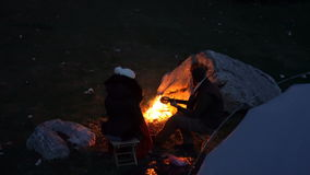 Couple of travelers at dusk near a campfire stock video