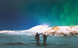 Couple Travelers enjoying Northern lights. View above mountains raised hands Travel Lifestyle and relationship men and women concept vacations into the wild Stock Photos