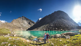 Couple of travelers at the gorgeous mountain lake royalty free stock images