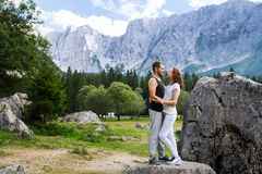 Couple of travelers on the Lago di Fusine lake with Mangart mountains in the background. Udine, Italy, Europe. Travel, Holidays, Freedom and Lifestyle Concept stock photos