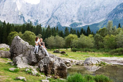 Couple of travelers on the Lago di Fusine lake with Mangart mountains in the background. Udine, Italy, Europe. Travel, Holidays, Freedom and Lifestyle Concept stock photography