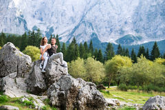 Couple of travelers on the Lago di Fusine lake with Mangart mountains in the background. Udine, Italy, Europe. Travel, Holidays, Freedom and Lifestyle Concept stock image